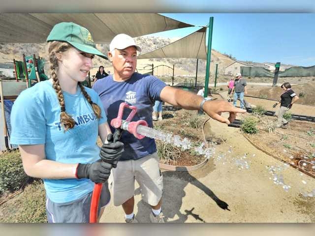 Volunteers Caleigh Paster, left, and Ben Dibene discuss the areas to be watered as volunteeers plant new flowers at a Habitat for Humanity event Saturday in Santa Clarita.