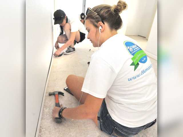 Circle of Faith volunteers Dezaray Frits, 16, and Beth Hawksworth nail base molding into place in a hallway.