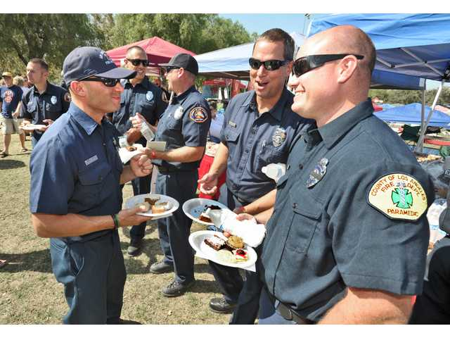 Firefighters from Los Angeles County Fire Station 111 enjoy plates of desserts during the First Responder Thank You Party held at Central Park in Saugus Saturday. Dan Watson / The Signal