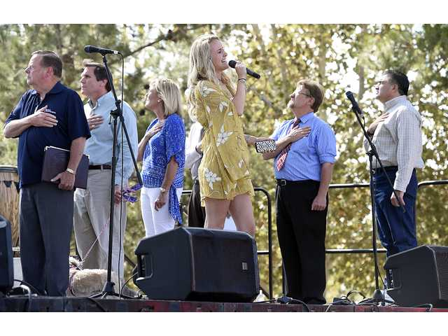 Savannah Burrow, center sings The National Anthem on stage as dignitaries salute the flag during the First Responder Thank You Party held at Central Park in Saugus Saturday. Dan Watson / The Signal