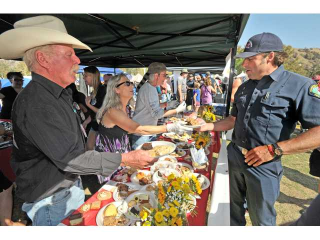 """""""Cowboy Mike"""" Gerrity, left, and members of the Sand Canyon community hand out cookies Los Angeles County Dozer Team One crew member Sean Ireland, right, during the First Responder Thank You Party held at Central Park in Saugus on Saturday. Photo by Dan Watson / The Signal"""
