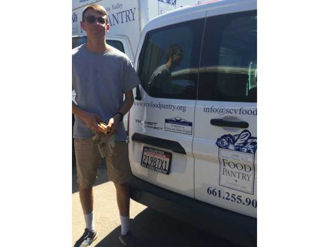 James Klipfel, Saugus High School senior, helped raised half the funds to buy a new van for the SCV Food Pantry. A sign on the vehicle is in memory of his grandparents. Courtesy photo