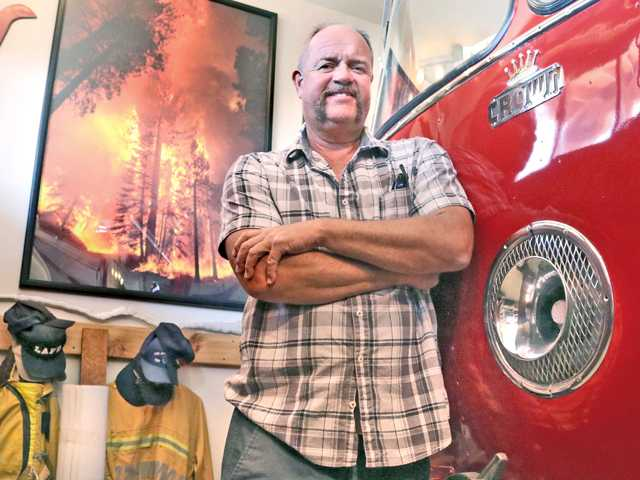 Jeff Zimmerman poses for the camera in front of his self-restored Crown Fire Truck from the 1950s with one of his photographs hanging in the background, at his home in Neenach. (Nikolas Samuels / The Signal)