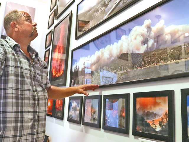 Jeff Zimmerman looks at the pictures he has taken in his 40 years of photographing fires at his home in Neenach. (Nikolas Samuels / The Signal)
