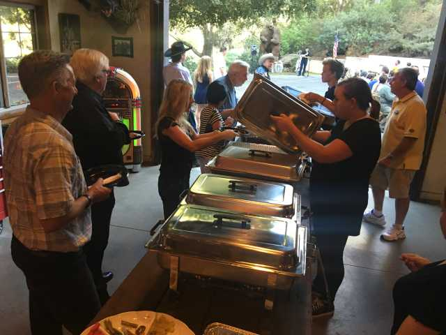 Attendees are served food at a barbecue which was held at Rancho Deluxe Film Studio in Canyon Country benifiting four firefighters and their families who lost their homes in the Sand Fire. On the menu Saturday evening was tri-tip, chicken, corn, beans and garlic toast. Food was served in the the Rancho Deluxe Man Cave filming set.