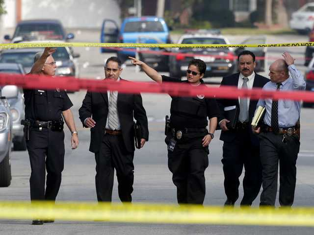 Law enforcement members look over the scene of an officer involved shooting in Torrance in 2013.