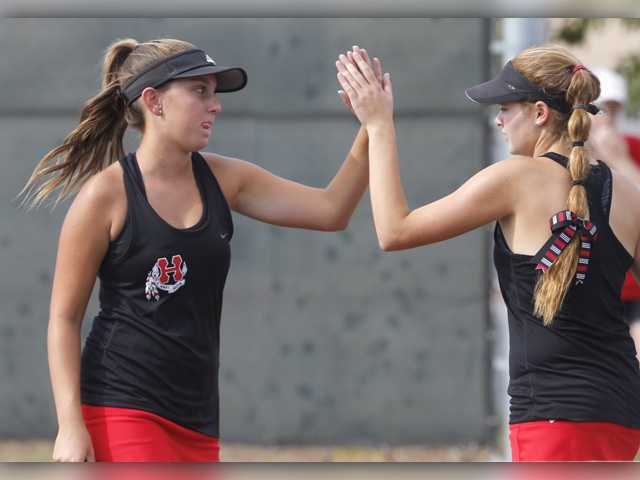 The Hart High No. 1 doubles team of Cameron Schwartz, left, and Sarah Backer, right, high-five between sets during their match against Golden Valley on the road on Tuesday. Signal photo by Katharine Lotze.
