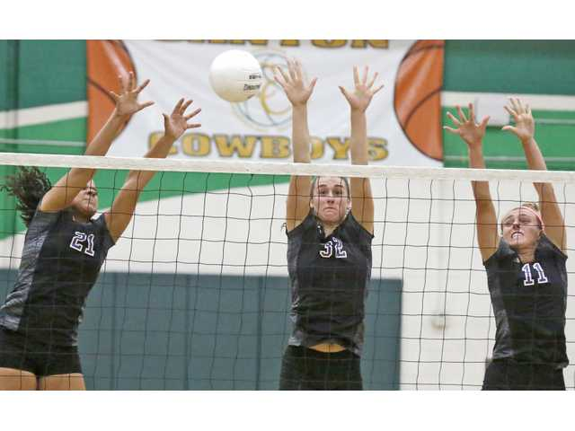 Valencia's Kaelyn White (21), Kayla Konrad (32), and Lauren Shockley (11) jump for a block during a volleyball game at Canyon High on Wednesday. Katharine Lotze/Signal