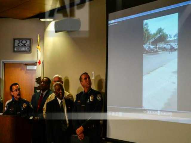 Authorities watch a video of the shooting scene at a news conference on Friday Sept. 30, 2016, in El Cajon, Calif, held to address the killing of Alfred Olango, a Ugandan refugee shot by an El Cajon police officer on Tuesday. The El Cajon police department released video footage of the shooting at the news conference. (AP Photo/Denis Poroy)