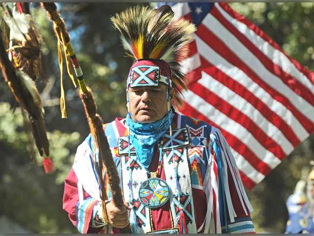 United States Marine Corps veteran Casey Fox carries the eagle staff to begin the dancing at the 23rd Annual Hart of the West PowWow & Native American Craft Fair held at William S. hart park in Newhall on Saturday. Dan Watson/The Signal