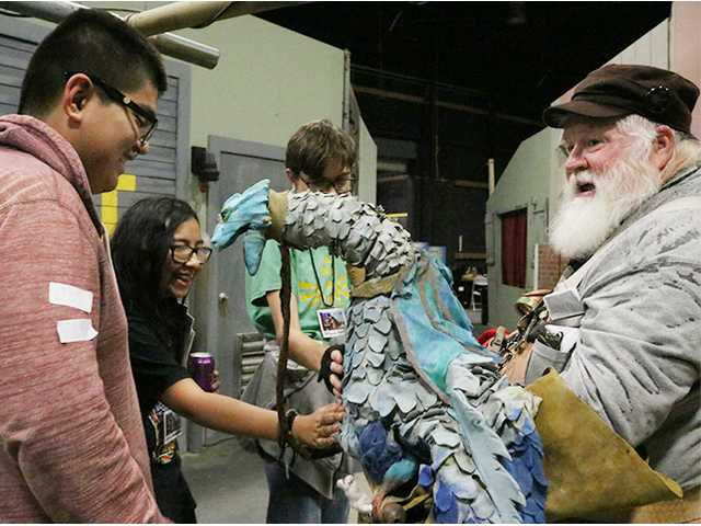 Jessica Hernandez and Nathaniel Champigny feel the heartbeat of Mike McCauley's Celtic water dragon as Ismael Lovera (left) watches over them at SCV Comic Con in Castaic on Saturday. Nikolas Samuels/The Signal
