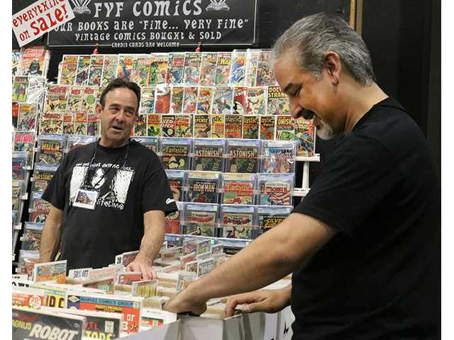 Brad Sloan (left) watches over Norm Rapmund, an artist with DC Comics, as he browses through comic books at SCV Comic Con in Castaic on Saturday. Nikolas Samuels/The Signal