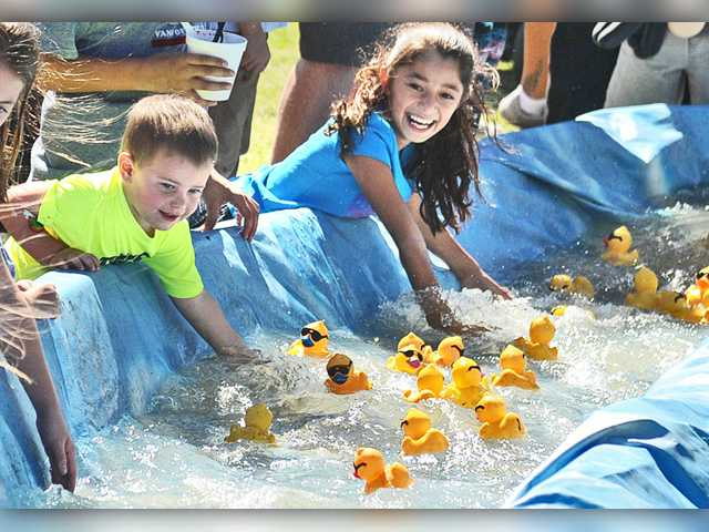 Children watch as the ducks are released during the second race of the 14th Annual Rubber Ducky Festival to benefit  the Samuel Dixon Family  Health Center held at Bridgeport Park in Valencia on Saturday.  Dan Watson/The Signal