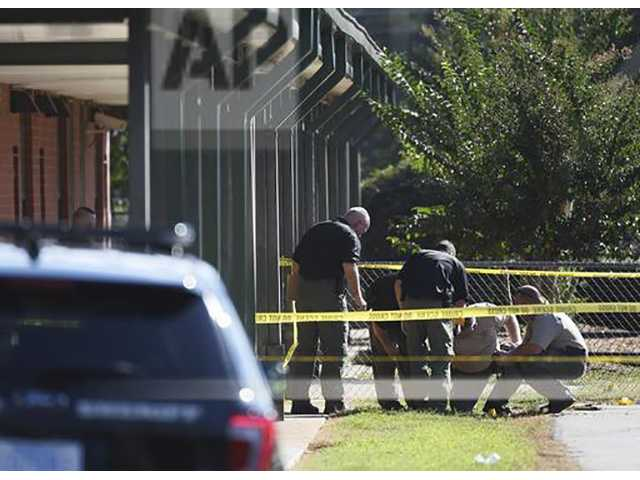 In this Wednesday, Sept. 28, 2016 file photo, members of law enforcement investigate an area at Townville Elementary School in Townville, S.C. A 6-year-old boy who was critically wounded in the school shooting died Saturday, Oct. 1, 2016, days after a 14-year-old boy opened fire on the school playground, authorities said. Jacob died about 1 p.m. Saturday, and an autopsy will be done Sunday, Anderson County Coroner Greg Shore said. (AP Photo/Rainier Ehrhardt, File)