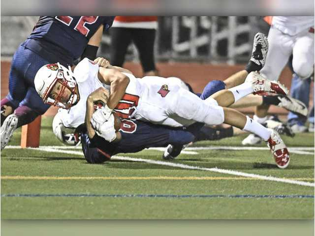 Santa Clarita Christian's Seth Yu (20) falls into the end zone to score in the first half against Trinity Classical Academy at Canyon High School on Saturday. Dan Watson/The Signal