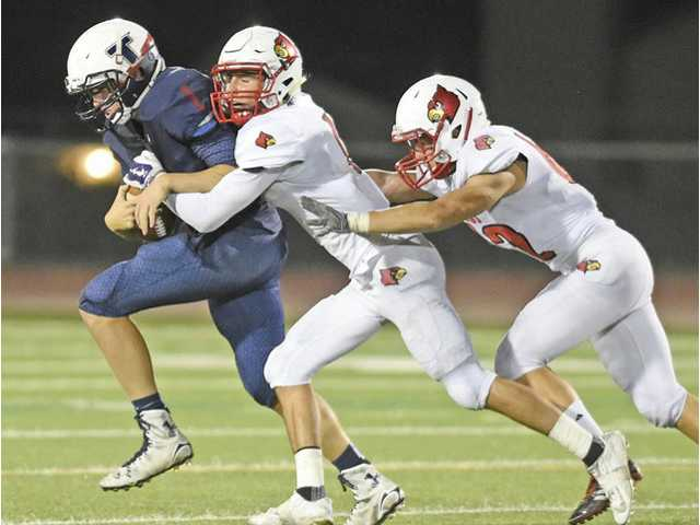 Trinity quarterback Tyler Lee (9), left, is sacked by SCCS defenders Aidan Espinosa (1) and Bryan Hixson (62) on Saturday. Dan Watson/The Signal