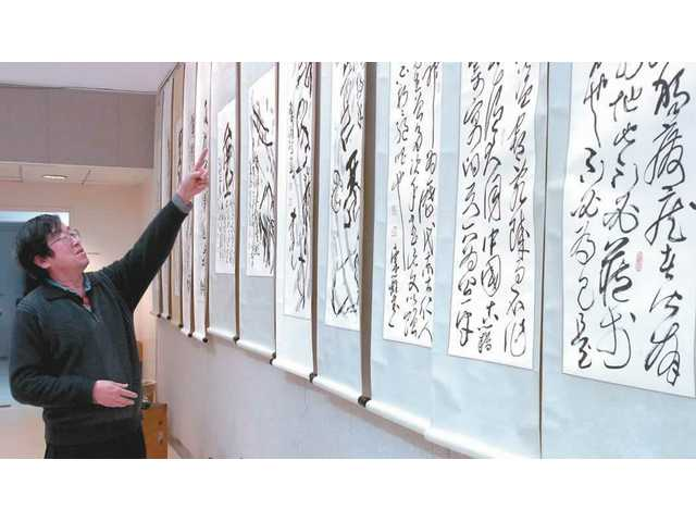 Dong-li Yan, a renowned Chinese Oracle Bone Script calligrapher visiting the United States for the first time, is describing one of his 41 pieces of calligraphy works on display at the Valencia public library. It is the first - and potentially only - display of Yan's work in the United States.03