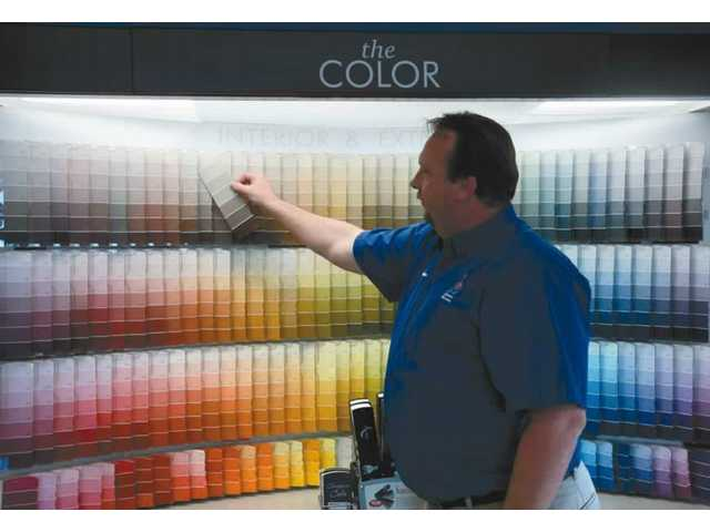 Sherwin-Williams Store Manager Sean Bingham compares color samples at his Canyon Country store.