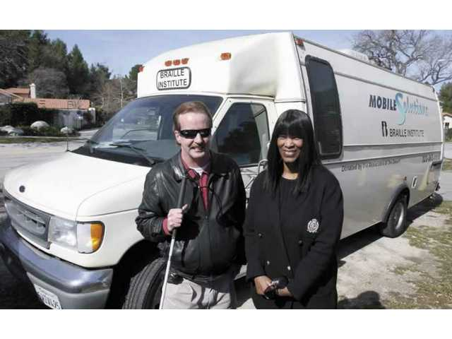 John Taylor, who heads up the Visually Impaired Assisted Services at the SCV Senior Center, and Sharon Ziegler, field services coordinator for the Braille Institute in Los Angeles County, stand before the Mobile Solutions Van that travels the county helping seniors.