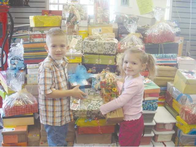 Jacob and Kennedy Schoenert help prepare the care packages as part of the Giving Respect and Nurturing Deserving Seniors (GRANDS) Project.