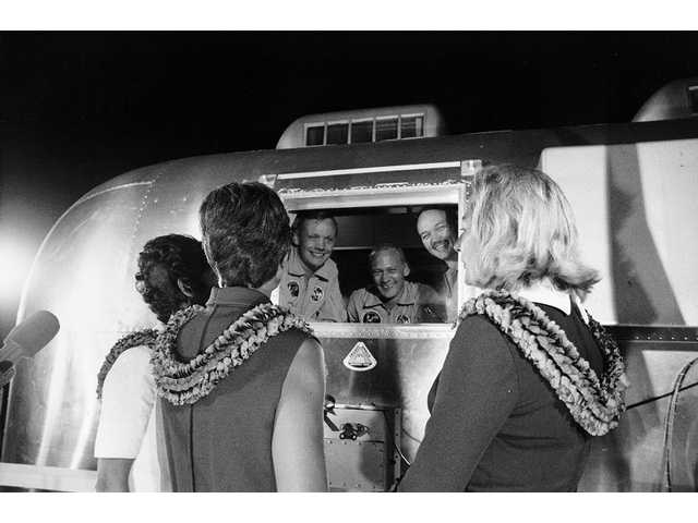 Apollo 11 astronauts, still in their quarantine van, are greeted by their wives upon arrival at Ellington Air Force Base.