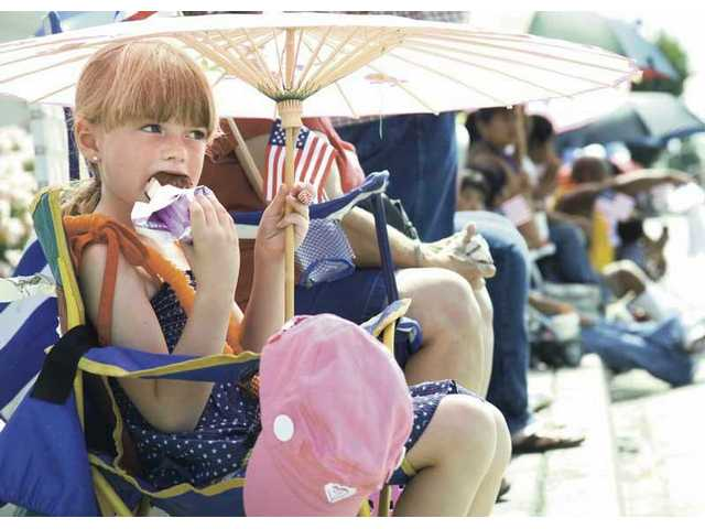 A girl beats the heat with an umbrella and ice cream sandwich at the 2008 Santa Clarita Fourth of July parade in Newhall.