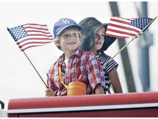 Kids wave flags as they ride in the bed of a pickup truck during a recent Santa Clarita Fourth of July parade in Newhall.