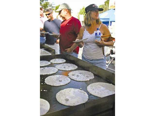 SCV Rotarians flip flapjacks for as many as 700 hungry parade-goers before the procession begins at 9 a.m., an hour earlier this year.