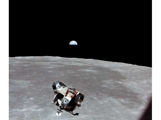 LM approaches CSM for docking with earthrise in the background.