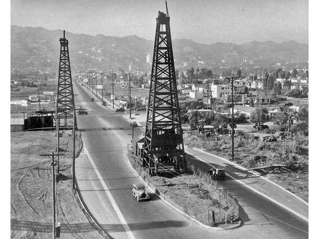 The road is paved around the still-producing oil wells on La Cienega Blvd. near Third Street, circa 1930s.