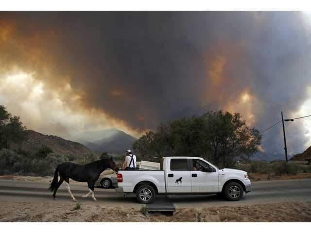Residents help Roberto Bombalier evacuate a 2-year-old horse on foot as the Station fire burning in the Angeles National Forest above Acton, Calif. on Sunday Aug. 30, 2009. The horse had not been trained for trailer travel yet.