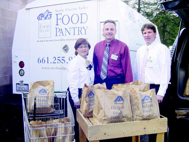 Albertsons store managers Michelle McLeod, Brian Gilman and Phil Martini deliver ham and turkey dinners to the Pantry.