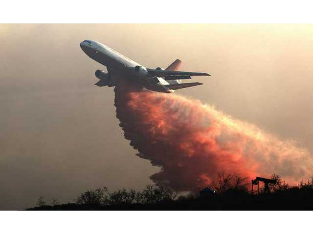 A DC-10 drops fire retardant over a hillside to battle wildfires in Grimes Canyon in Fillmore, Calif., on Tuesday, Sept. 22, 2009.