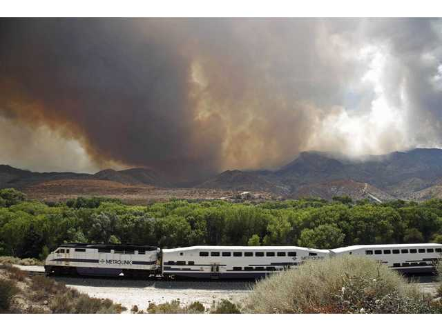 A Metrolink commuter train heads north on the Antelope Valley line as the Station fire burns in the Angeles National Forest above Acton, Calif. on Sunday Aug. 30, 2009.