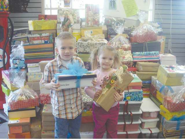 Brother and sister Jacob and Kennedy Schoenert help prepare the care packages as part of the GRANDS Project.