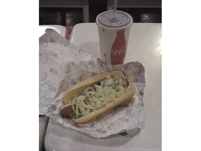 A hot dog loaded with onions and a variety of condiments is available for purchase by members of the Costco Warehouse in Canyon Country at a budget-friendly $1.50 with a 20-ounce soda (with refill).