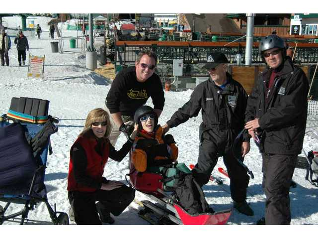 La Mesa student Trent DiMauro, in sled, with volunteer instructors from the United States Adaptive Recreation Center and his mother.