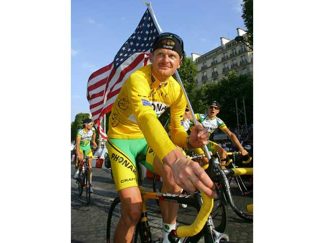 FILE - In this July 23, 2006 file photo, Tour de France winner Floyd Landis of the US waves the US flag as he rides up the Champs-Elysees avenue in Paris following the final stage of the 93rd Tour de France cycling race between Antony, south of Paris, and Paris. France's anti-doping chief said on Monday Feb. 15, 2010 that a French judge has issued an international arrest warrant for U.S. cyclist Floyd Landis in connection with a case of data hacking at a doping laboratory.