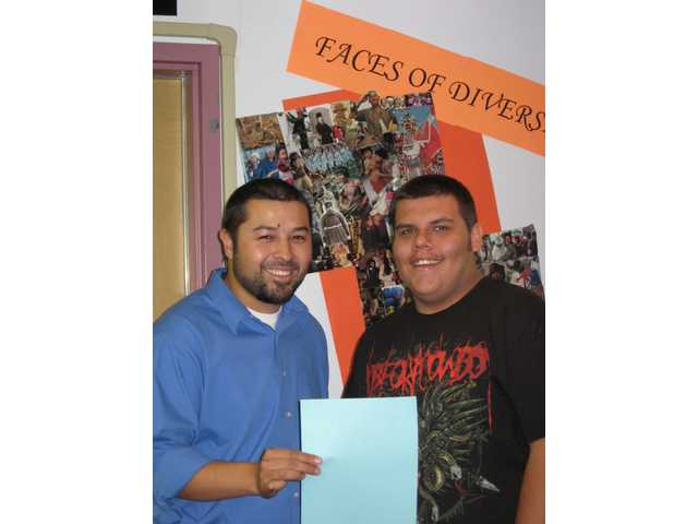Bowman teacher Jose Rosales (left) helps Dylan Calzada with the essay which gained him admission to this weekend's Institute.
