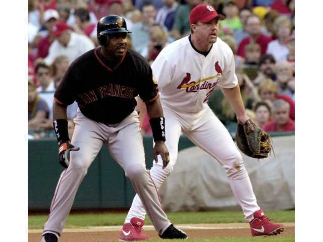 "FILE - In this June 22, 2001, file photo, San Francisco Giants' Barry Bonds, left, leads off first base next to St. Louis Cardinals first baseman Mark McGwire in the first inning of a baseball game in St. Louis. Home run king Bonds said he is ""proud"" of McGwire for returning to baseball as the Cardinals' hitting coach and for admitting his use of performance-enhancing drugs."