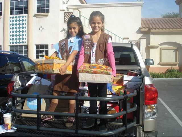 Two Brownies from Troop 68, left, help distribute gift-filled shoeboxes to seniors.
