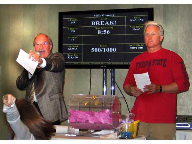 Auctioneer Don Fleming, left, points to a bidder in the crowd as co-auctioneer Rick Chambers, anchorman and reporter for CBS2/KCAL-9, watches at the Susan and Mike Gunning Family Benefit held Nov. 8 at the Hyatt Valencia.