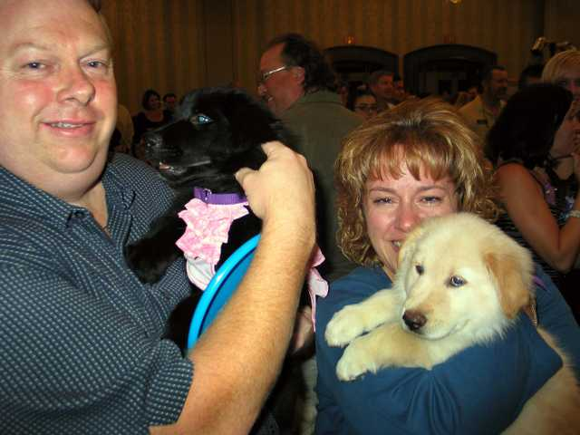 Pete and Dee Ferry hug puppies Hope and Faith at the Susanne and Mike Gunning Family Benefit. The couple were the high bidders for the puppies.