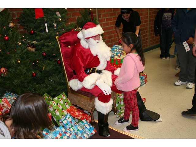 A young girl meets Santa Claus at Hart High School's holiday dinner on Friday night.