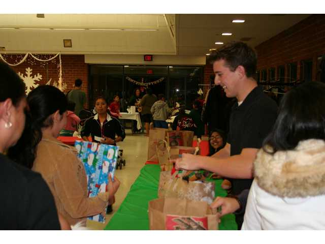 A volunteer passes out bags of canned food and clothes to familes who attended Hart High School's holiday dinner.
