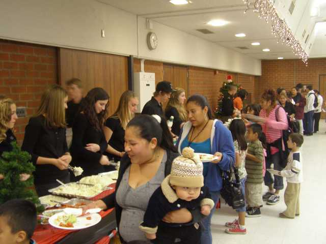 Families walk through a buffet line at Hart High School's holiday dinner on Friday night.