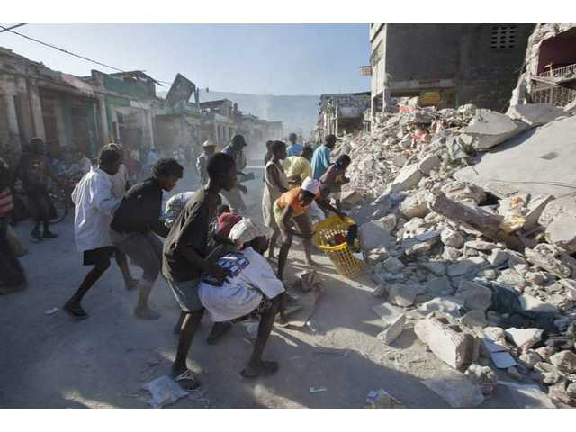 People fight over goods scavenged from the rubble of buildings collapsed during Tuesday's earthquake in Port-au-Prince, Friday, Jan. 15, 2010.
