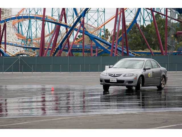 A driving instructor with Defensive Driving Academy demonstrates how to correct a vehicle sliding on wet pavement. Sunday's obstacle course taught drivers how to react when faced with sudden traffic hazards.