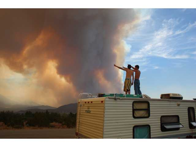Ronnie May, 19, and Steven Williams, 17, both of Acton, stand atop a trailer home pulled from an Acton RV park before dawn Sunday as the Station Fire advanced down the northeast slope of the San Gabriel Mountains. Thousand Trails, the members-only RV park where many residents lived full time, was among the areas under a mandatory evacuation due to the fire. May, Williams and other residents pitched in together to pull as many homes out of the path of the fire as possible.