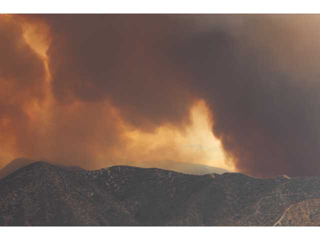 Smoke billows above the Station Fire on Sunday as it advances down the northeast side of the San Gabriel Mountains toward the town of Acton. Residents of Acton received reverse 911 calls early Sunday morning warning them to evacuate their homes, but many in the main part of town remained Sunday afternoon.